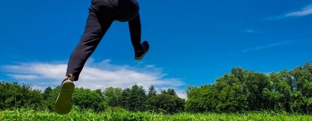 芝生の上で飛び越える男性